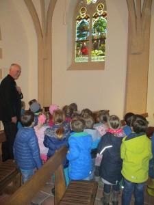 Die Vorschulkinder schauen sich mit Pfarrer Terlinden die Fenster der Hubertuskapelle an